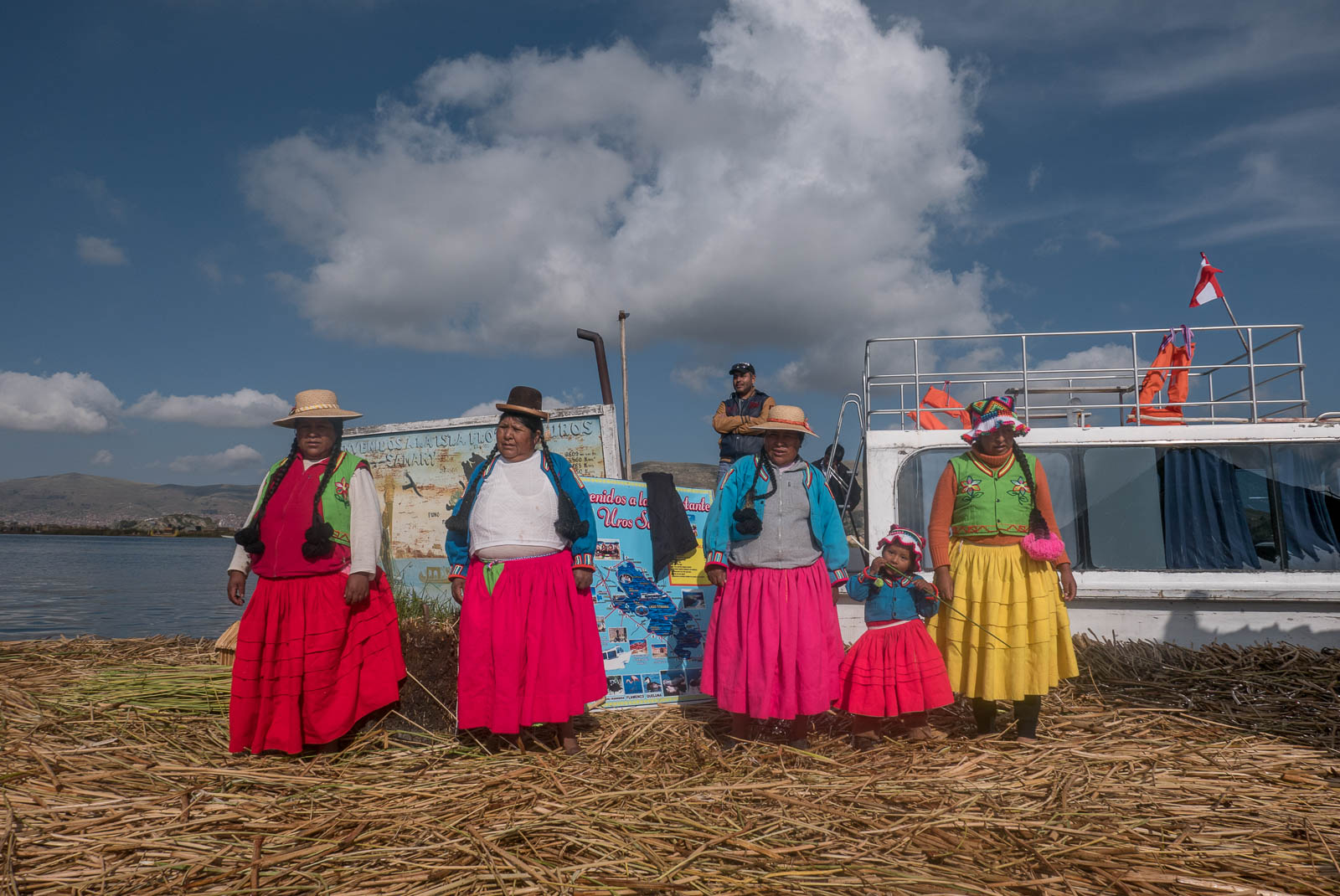 Three brightly coloured women of Uros Island, with a young three-year-old girl, show off their beautiful traditional dress on Uros Island.