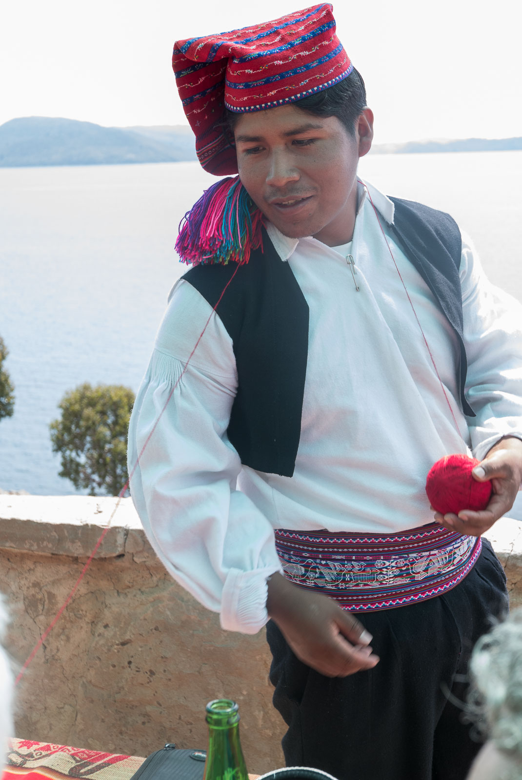 A man in traditional costume with a ball of wall, one of the professional knitters of Taquile Island.