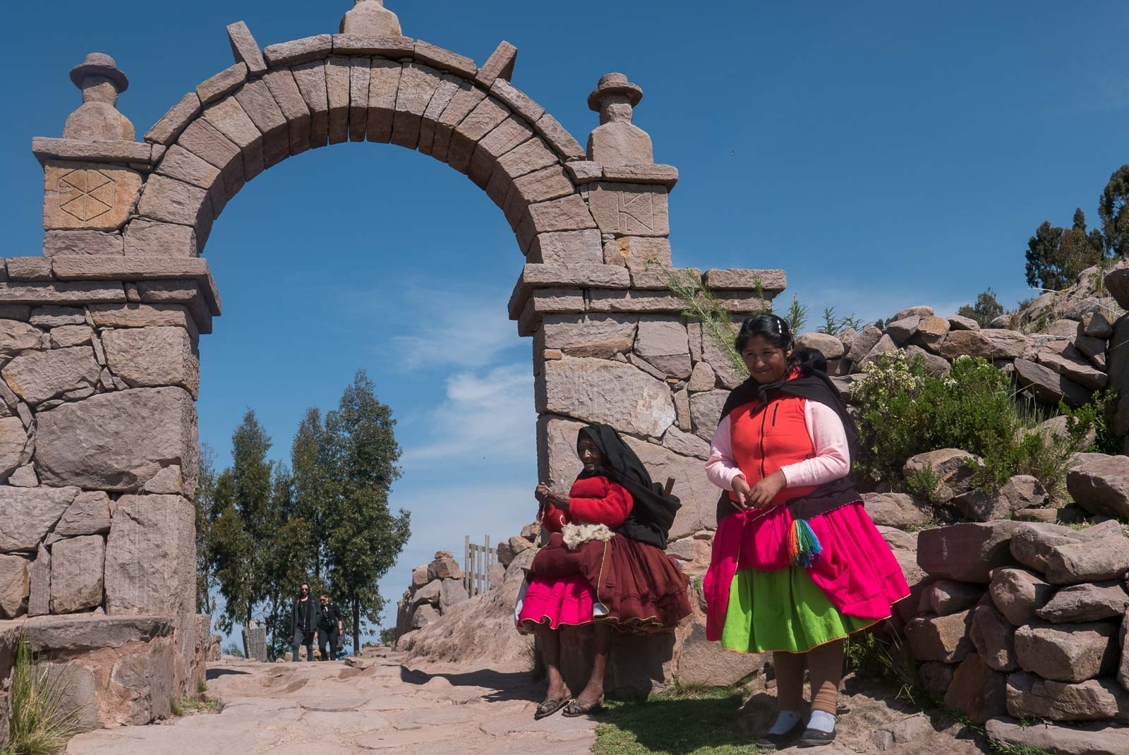Two local women, in traditional bright skirts at a stone arch on Taquile Island.