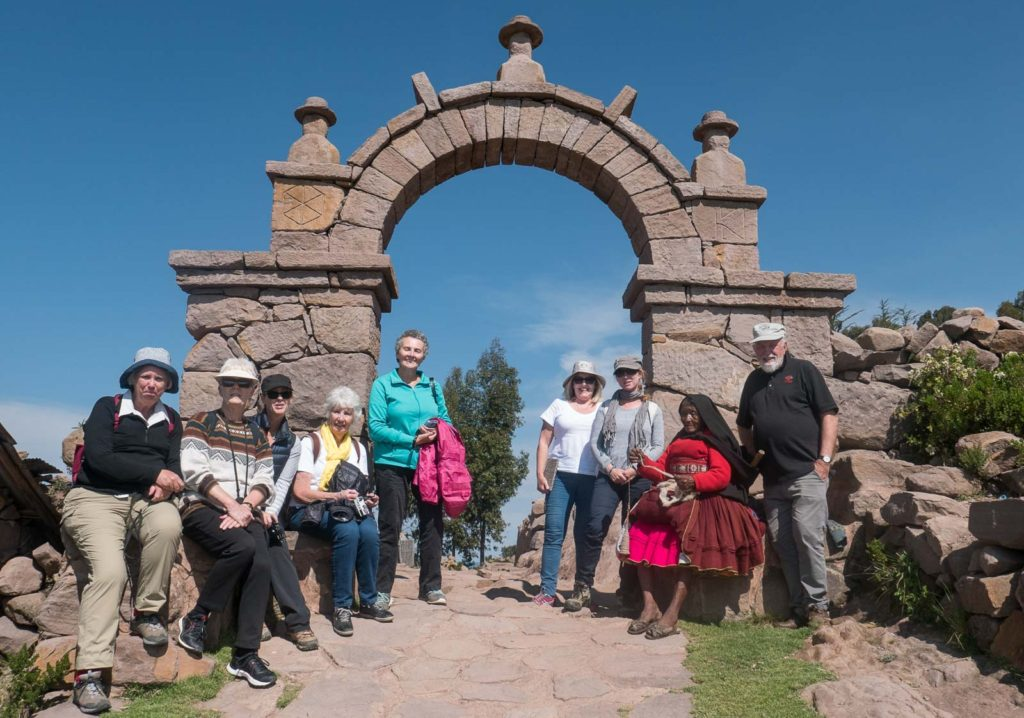 My Two's a Crowd tour group meets a local woman at a stone arch on Taquile Island, Lake Titicaca.