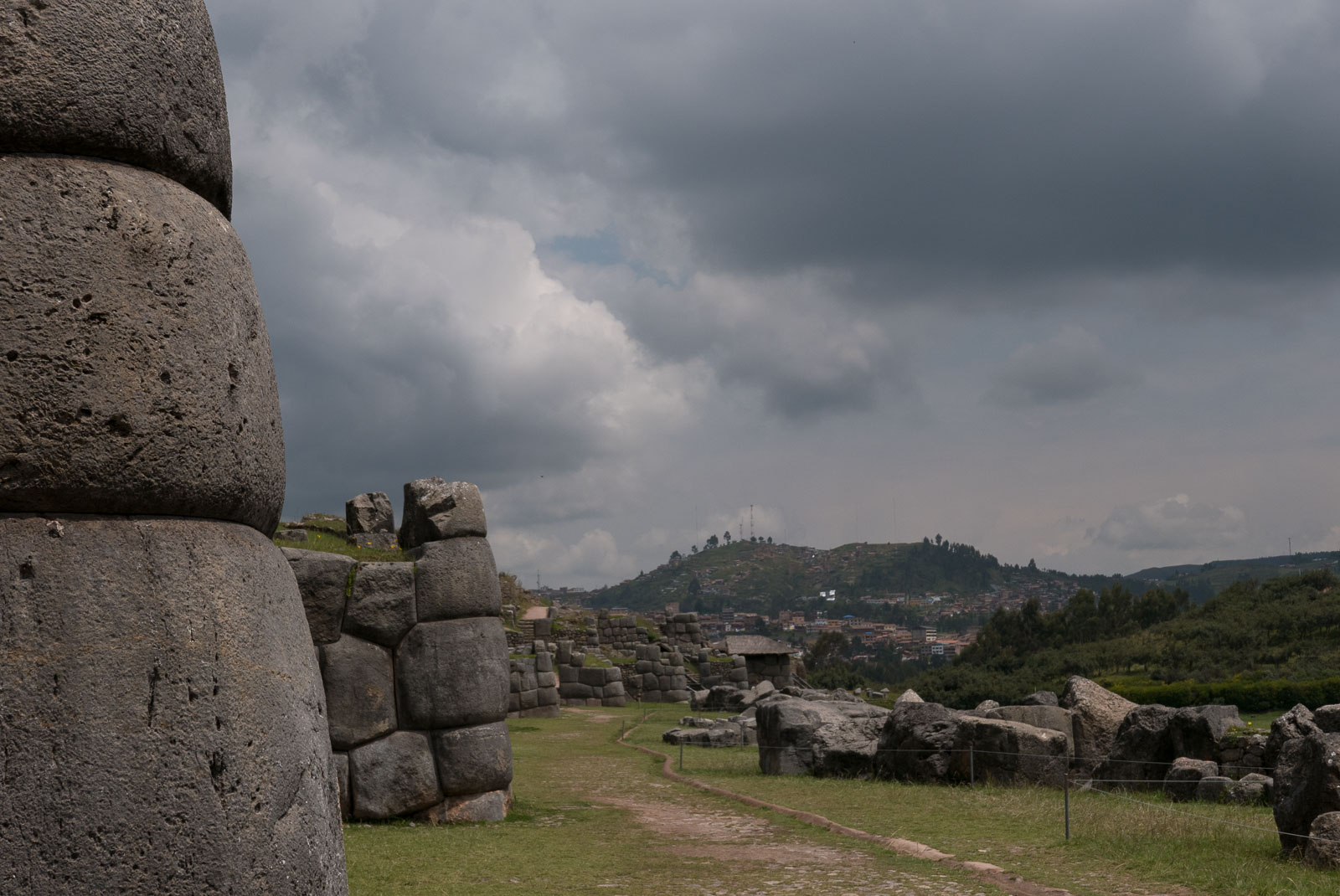 The imposing citadel rock walls at Sacsayhuaman, built around 1100, under a dark foreboding sky.