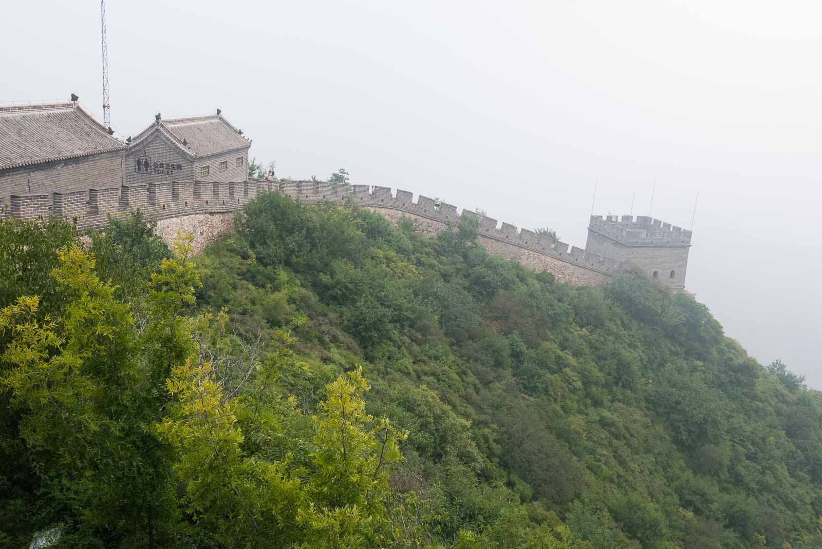 Great Wall of China, shrouded in mist and surrounded by greenery.