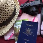 Passports, notebook, hat and camera - travel essentials.