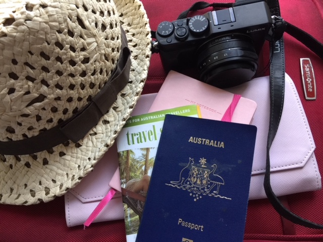 Passports, notebook, hat and camera - travel essentials.